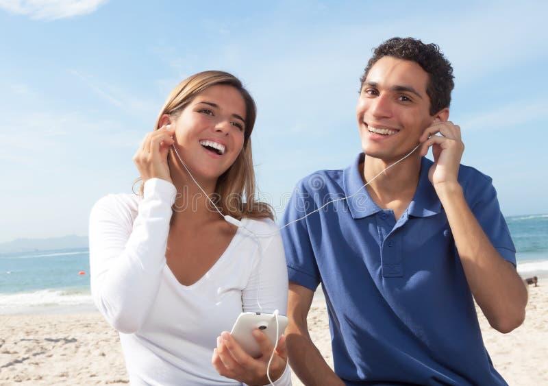 Jong paar die aan muziek van de telefoon luisteren royalty-vrije stock fotografie