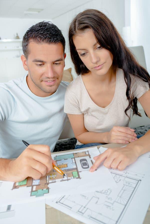 Jong paar die architectuurplannen controleren royalty-vrije stock fotografie