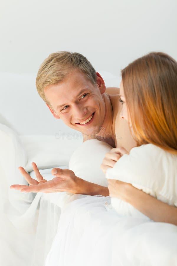 Jong paar die in bed babbelen stock foto's