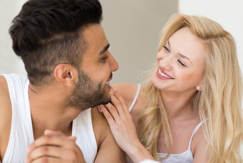 Jong Paar die in Bed liggen die elkaar, de Gelukkige Glimlach Spaanse Mens en Vrouwenclose-up bekijken stock fotografie