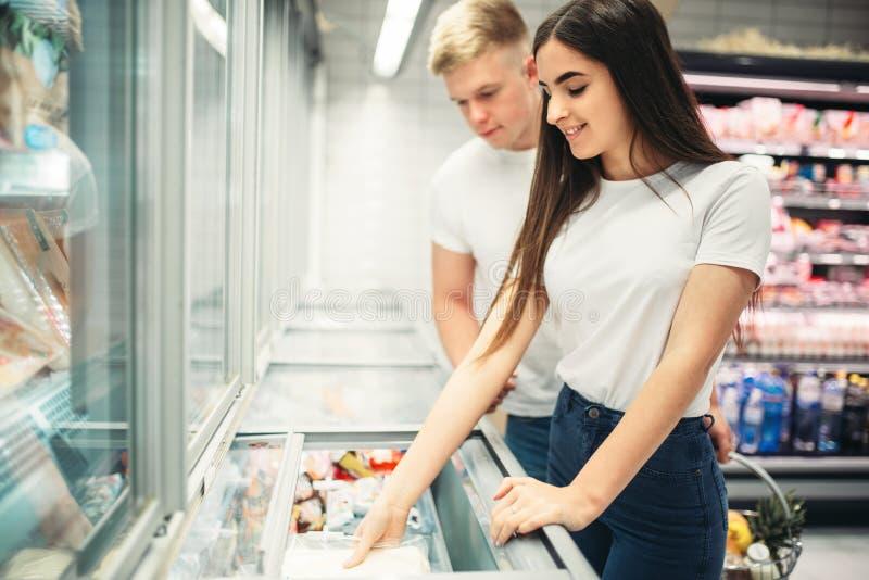 Jong paar die bevroren goederen in supermarkt kiezen royalty-vrije stock foto