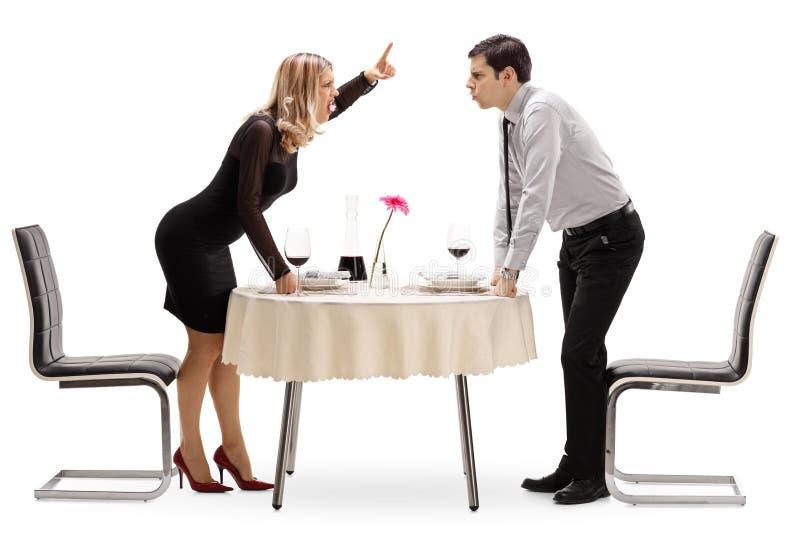 Jong paar die bij een restaurantlijst debatteren stock afbeelding