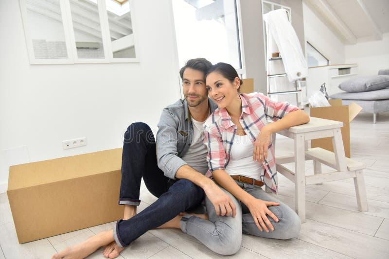 Jong paar die bij hun nieuw huis gelukkig voelen stock fotografie