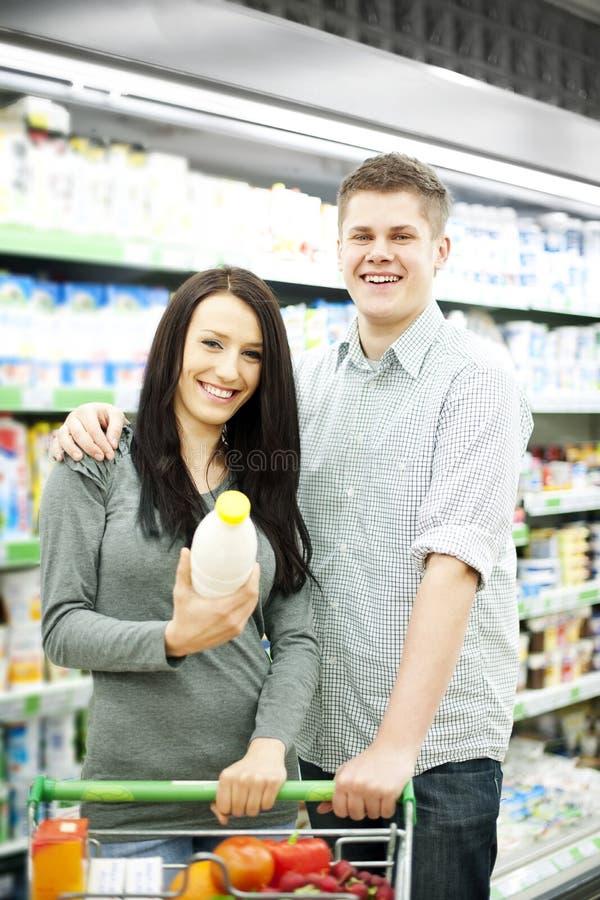 Jong paar die bij supermarkt winkelen stock foto