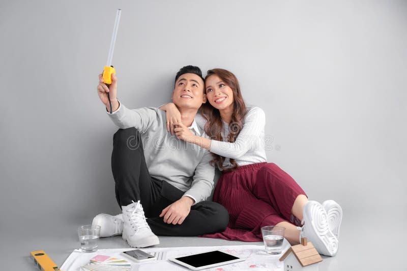 Jong paar die blauwdrukken van zij onderzoeken nieuw huis Onroerende goederen en Bewegend huisconcept royalty-vrije stock foto's