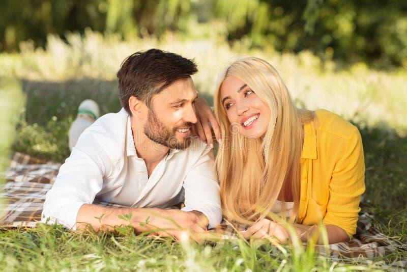 Jong paar die datum hebben tijdens picknick in park royalty-vrije stock afbeelding
