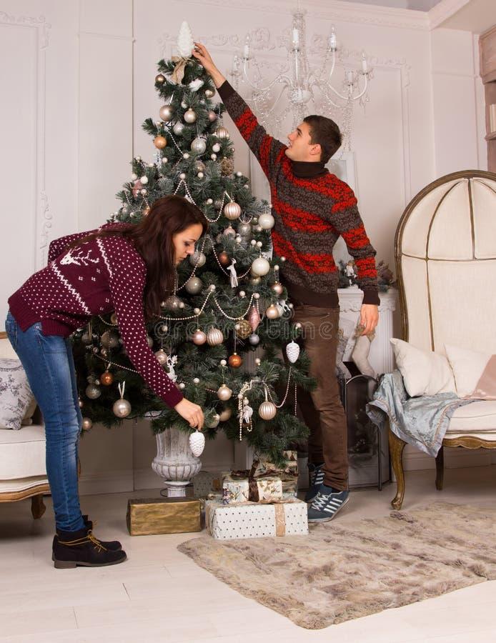 Jong paar die de Kerstboom verfraaien royalty-vrije stock afbeelding