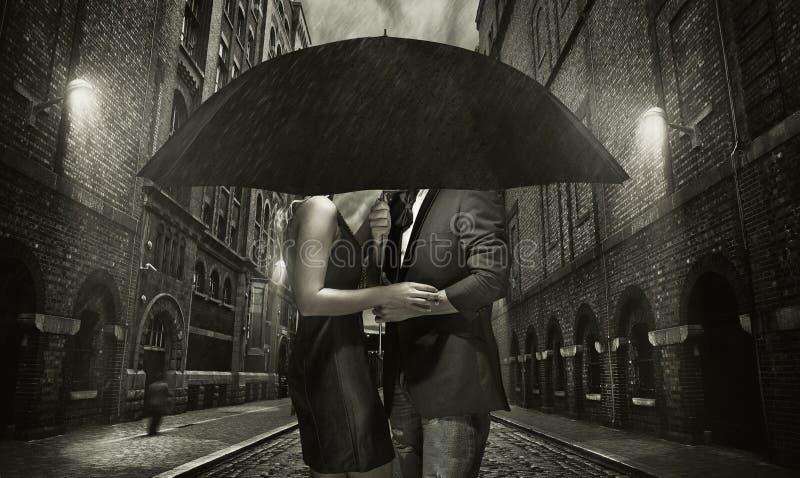 Jong paar die in de regen koesteren royalty-vrije stock foto's