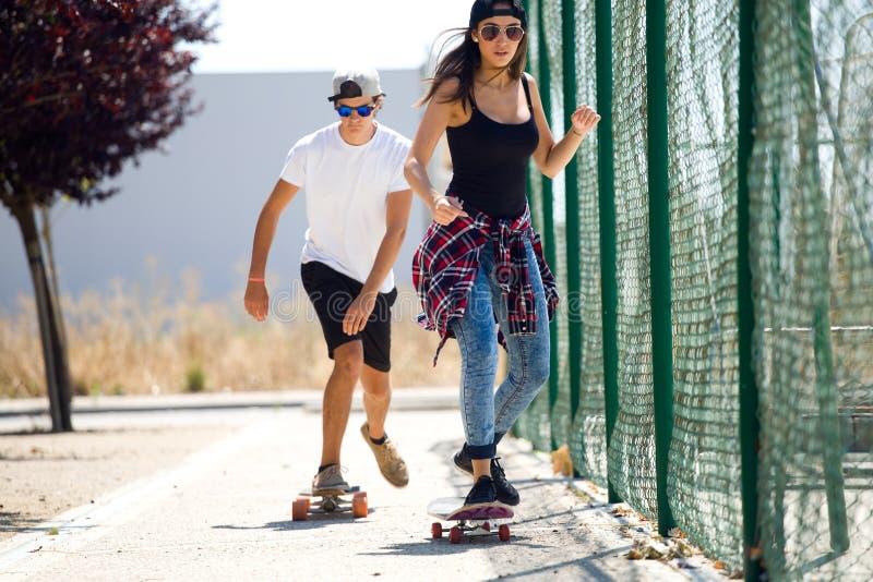 Jong paar die in de straat met een skateboard rijden royalty-vrije stock foto's