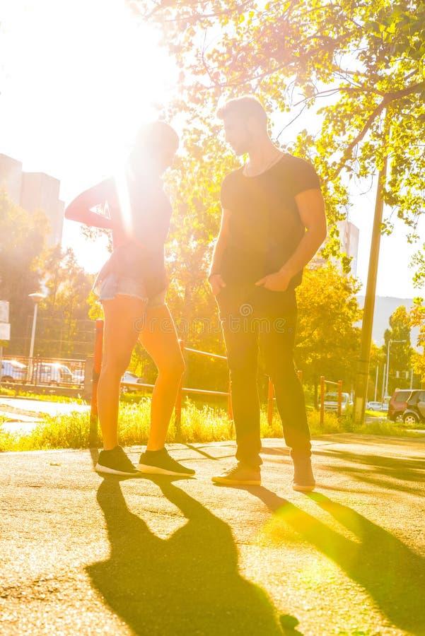 Jong paar die in de zonsondergang in een stedelijk milieu spreken stock afbeelding
