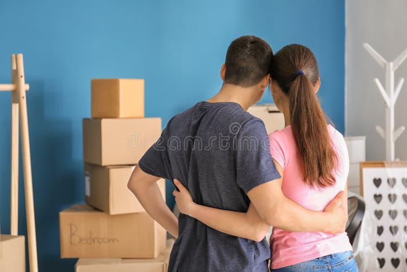 Jong paar die dichtbij dozen zich binnen bevinden Het bewegen zich in Nieuw Huis royalty-vrije stock afbeeldingen