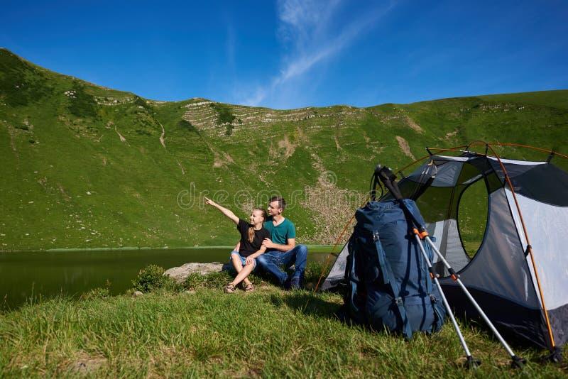 Jong paar die dichtbij het kamperen tegen meer in bergen bij de zomerdag rusten stock afbeeldingen