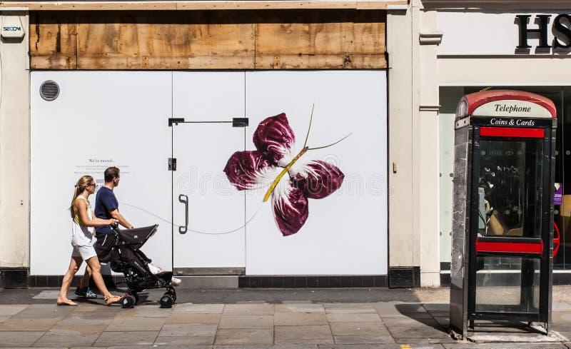 Jong paar die die met een kinderwagen voor een muur lopen met een grote vlinder wordt verfraaid stock afbeeldingen