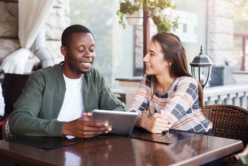 Jong paar die digitale tablet in koffie gebruiken stock afbeelding