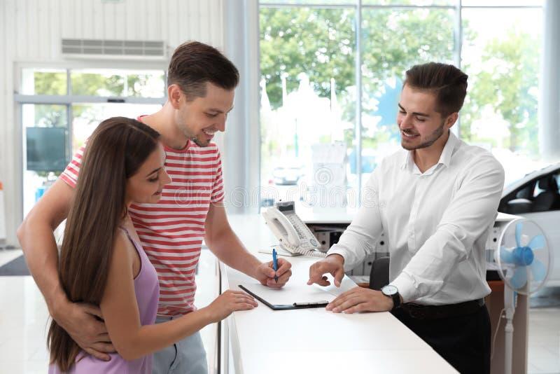 Jong paar die documenten ondertekenen stock afbeeldingen