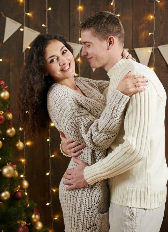 Jong paar die in donker houten binnenland met lichten koesteren Romantisch avond en liefdeconcept De vakantie van het nieuwjaar K royalty-vrije stock afbeeldingen