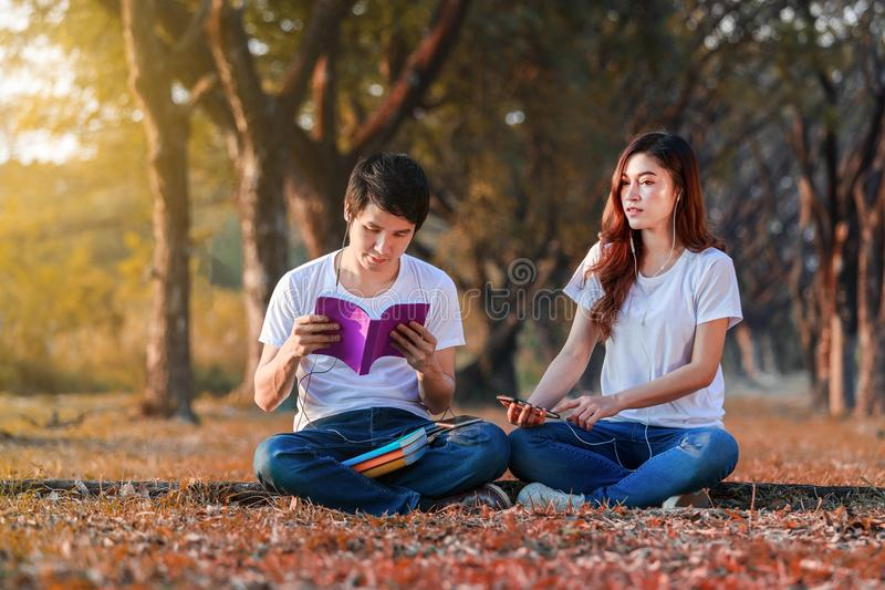 Jong paar die een boek en het luisteren muziek met oortelefoons i lezen stock afbeeldingen