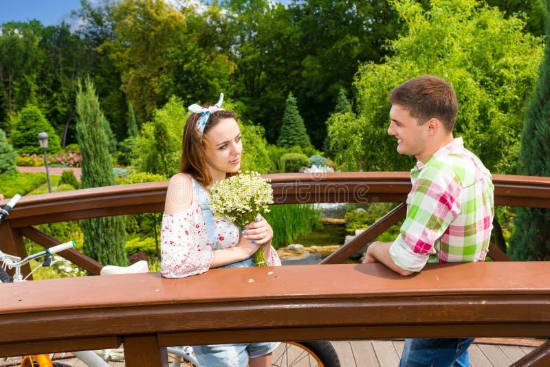 Jong paar die een datum op een brug in het park hebben stock afbeelding
