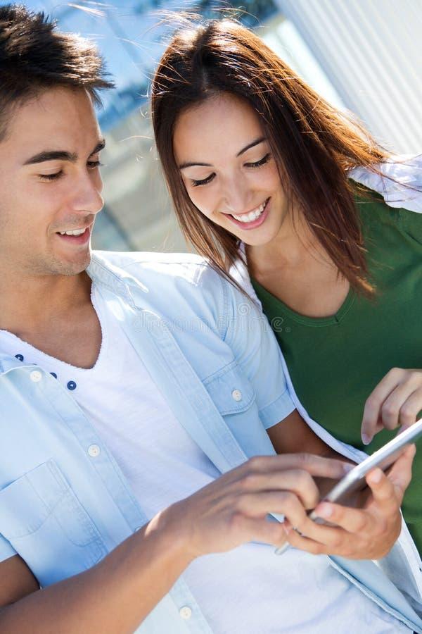 Jong paar die een digitale tablet gebruiken stock foto's