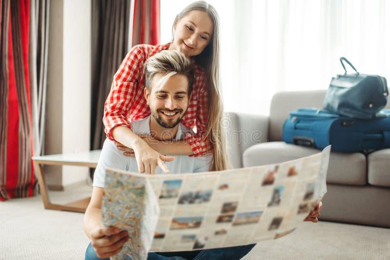Jong paar die een kaart bestuderen vóór de zomerreis royalty-vrije stock fotografie