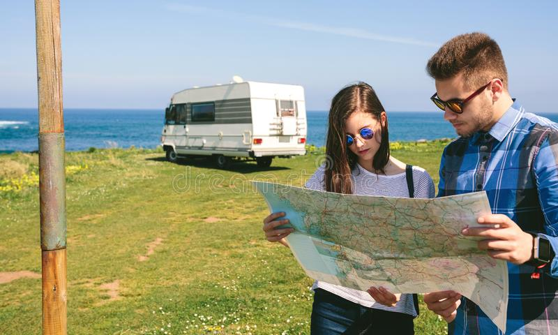 Jong paar die een kaart dichtbij de kust kijken royalty-vrije stock fotografie