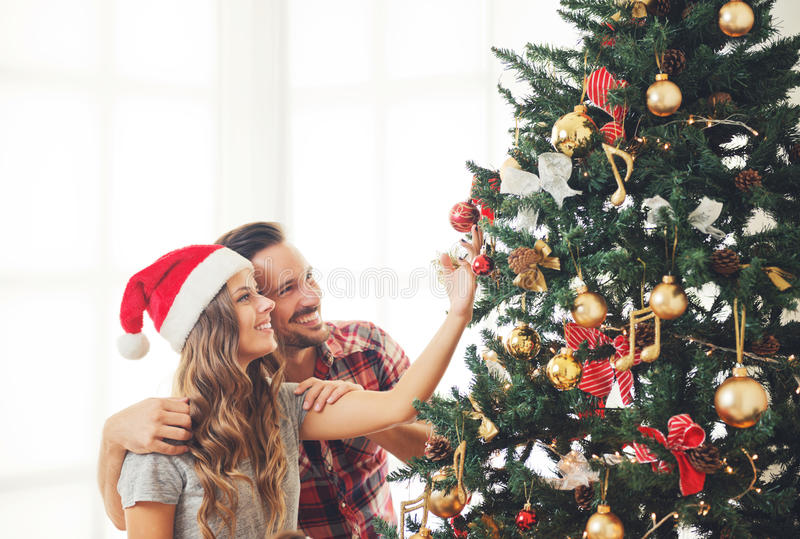 Jong paar die een Kerstboom verfraaien stock fotografie