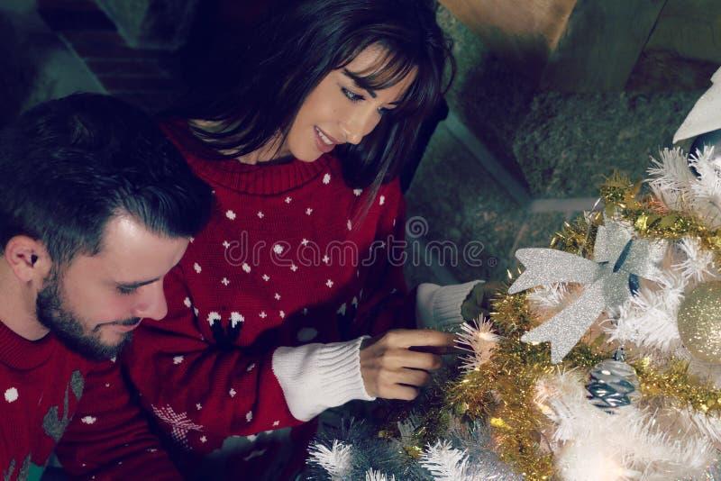 Jong paar die een Kerstboom verfraaien stock foto's