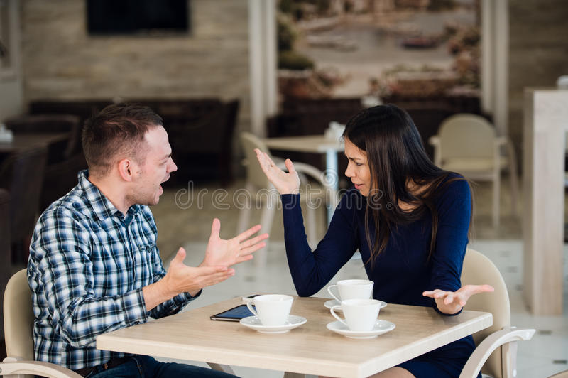 Jong paar die in een koffie debatteren Zij ` s had genoeg, verontschuldigt de vriend zich Jong paar die, het schreeuwen ruzie mak royalty-vrije stock foto
