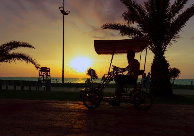 Jong paar die een romantische fiets achter elkaar langs de strandboulevard berijden bij zonsondergang royalty-vrije stock foto