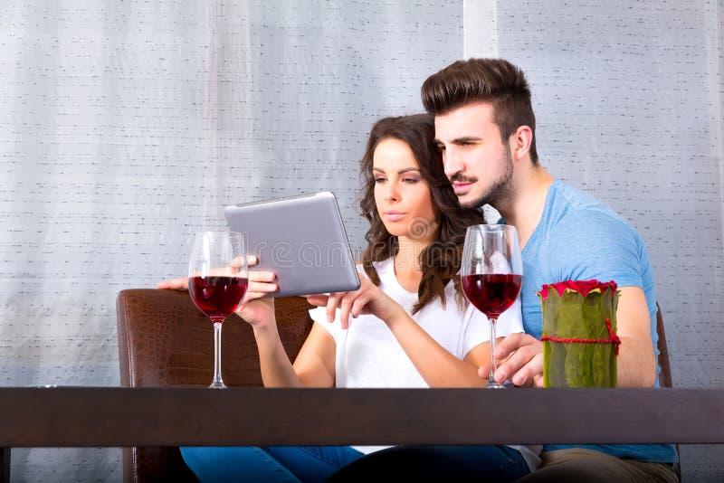 Jong paar die een Tabletpc met behulp van terwijl het hebben van een glas wijn stock fotografie