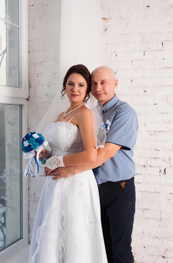 Jong paar die en een huwelijkskleding huwen spelen elkaar trouwringen en zeer gelukkig royalty-vrije stock foto