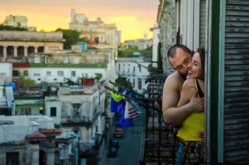 Jong paar die en op een balkon koesteren kussen stock afbeeldingen