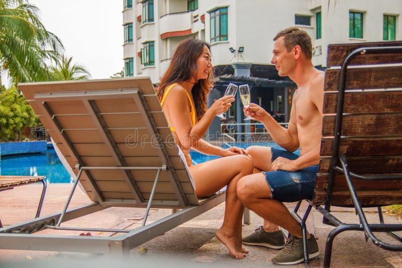 Jong paar die en op sunbeds, de zomervakanties en het drinken champagne zonnebaden liggen stock foto