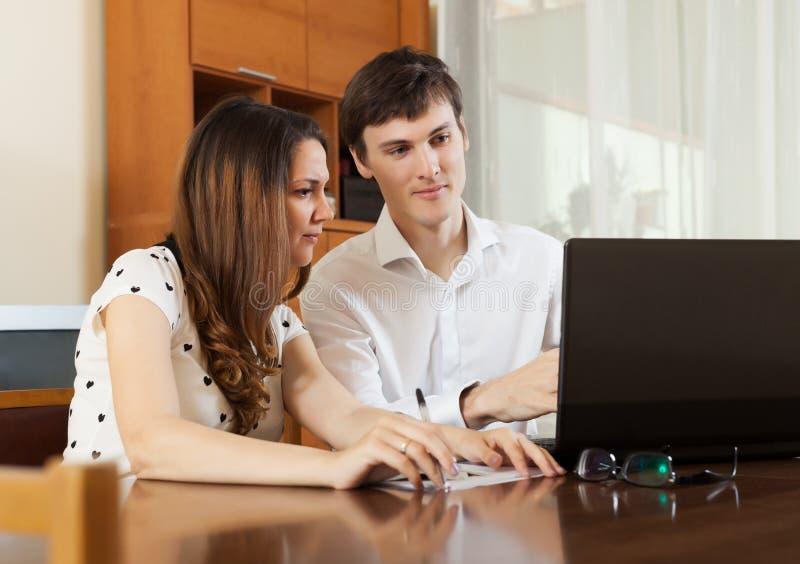 Jong paar die financiële documenten in laptop kijken royalty-vrije stock fotografie