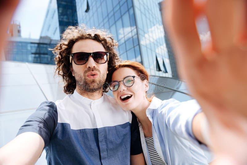 Jong paar die glazen dragen die terwijl het maken selfie lachen stock afbeelding