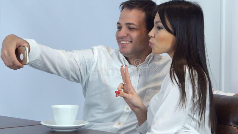 Jong paar die grappige selfies op de telefoon in een koffie nemen royalty-vrije stock afbeelding