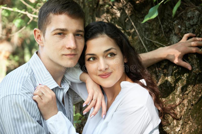 Jong paar die in het bos lopen, die dichtbij boom, de zomeraard, helder zonlicht, schaduwen en groene bladeren, romantisch gevoel royalty-vrije stock foto