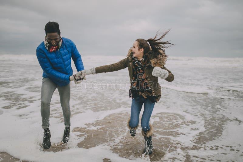 Jong Paar die in het Overzees van het de Winterstrand lachen royalty-vrije stock foto's