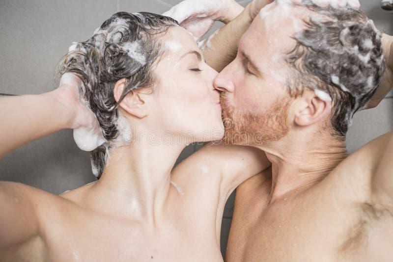 Jong paar die hun hoofden in de douche wassen stock fotografie
