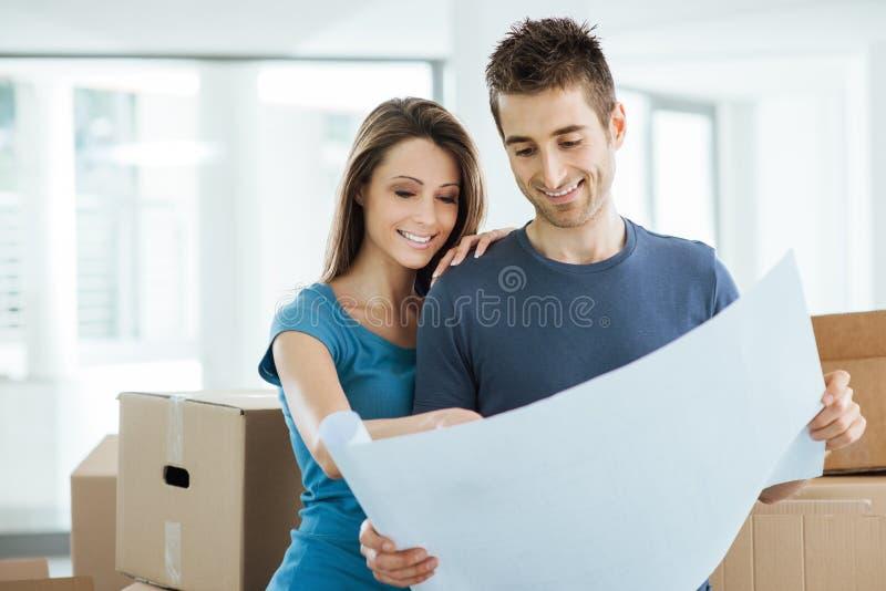 Jong paar die hun nieuw huis plannen royalty-vrije stock afbeeldingen
