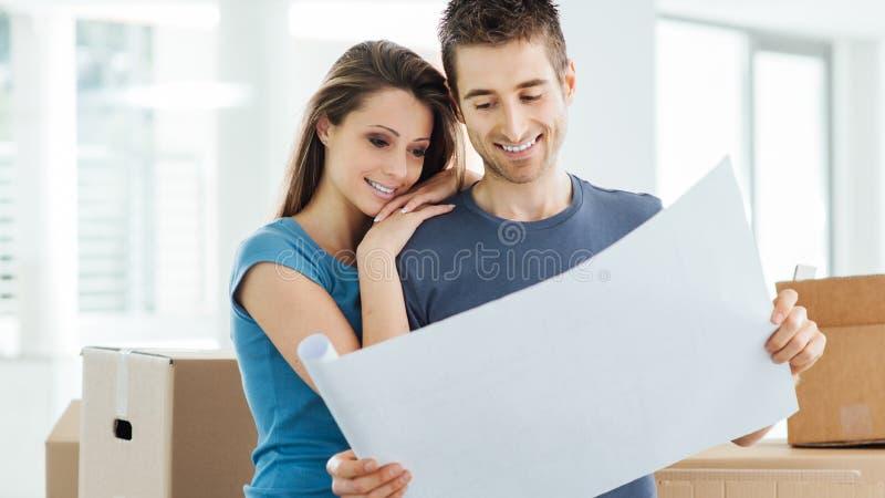 Jong paar die hun nieuw huis plannen stock afbeelding