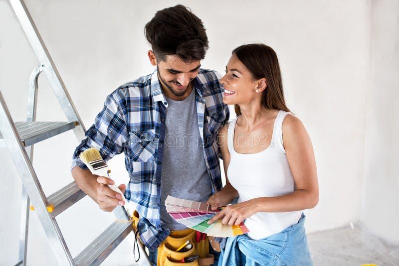 Jong paar die kleuren voor het schilderen van hun nieuw huis kiezen royalty-vrije stock foto