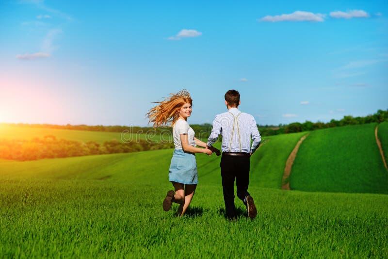 Jong paar die langs een groen gebied op een mooie zonnige dag lopen stock foto