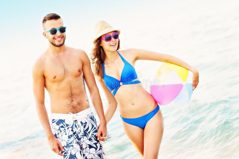 Jong paar die langs het strand lopen stock foto's
