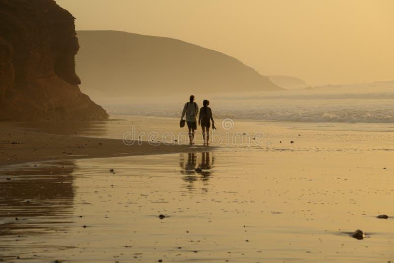Jong paar die langs het strand lopen royalty-vrije stock foto's