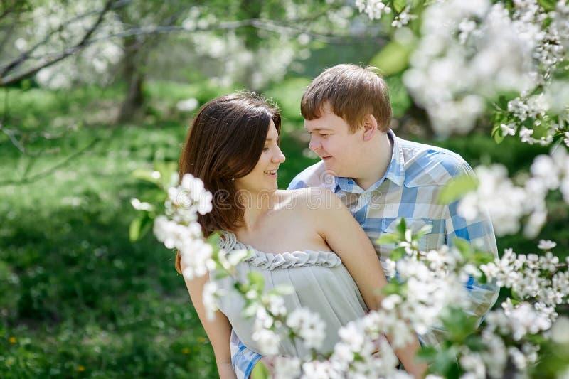 Jong paar die in liefde in de tuin van de bloesemlente lopen royalty-vrije stock foto