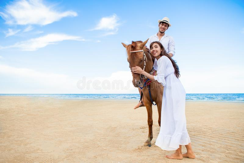 Jong paar die in liefde met het paard op zee strand lopen op blauwe hemel wittebroodsweken tropische overzeese de zomervakantie b royalty-vrije stock foto's