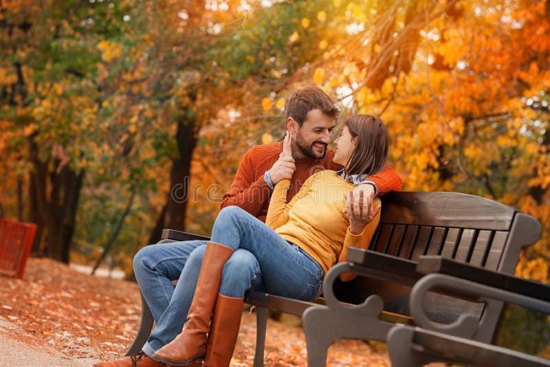 Jong paar die in liefde op bank in de herfstpark flirten royalty-vrije stock afbeeldingen