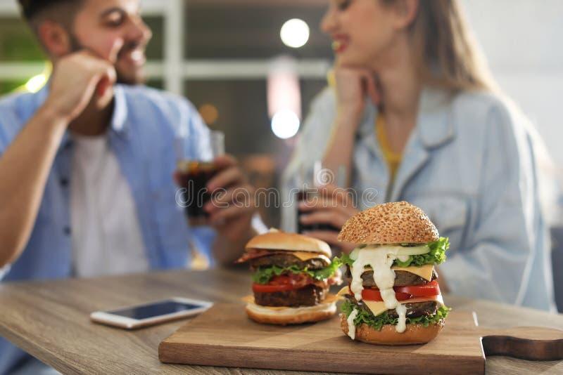 Jong paar die lunch in restaurant, nadruk op burgers hebben stock foto