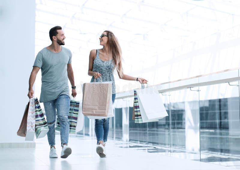 Jong paar die met het winkelen zakken iets bespreken royalty-vrije stock foto